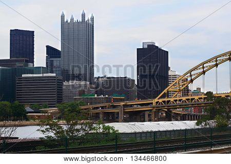Skyline of downtown Pittsburgh Pennsylvania. Administrative and high rising office buildings. Visible is Monongahela River with moored transport barge bridges and Highways.
