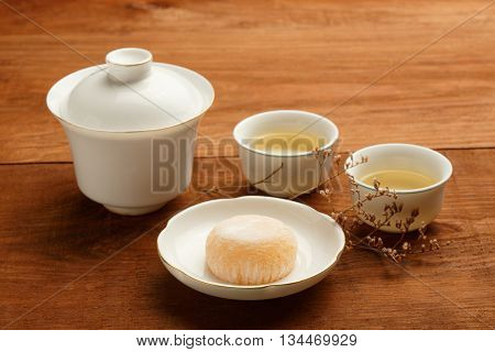 Gaiwan and cups of white chinese porcelain with green tea standing on wooden table with delicious japanese mochi rice cake on white plate decorated with dried flower. Shallow dof focus on foreground.
