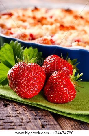 Three Fresh Red Strawberries In Front Of Fruit Cake On Green Towel