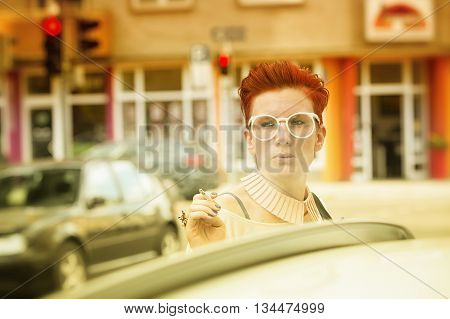 red-haired woman standing in the street and smoking a cigarette