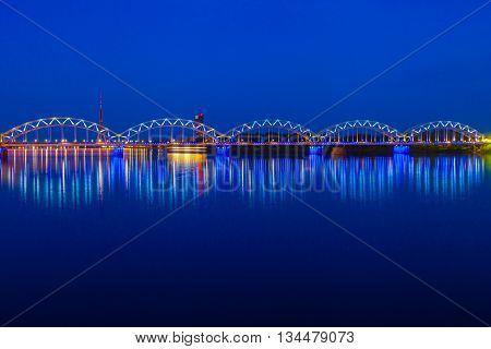 Illuminated Railway Bridge And Reflection In Daugava River At Twilight. Riga, Latvia