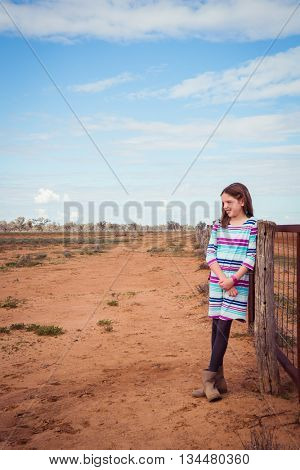 Young girl leaning on a fence in the dry drought ridden outback australia