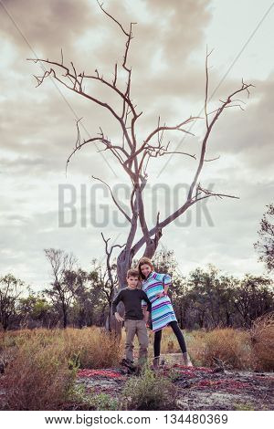 Brother and sister standing in front of an old tree in outback Australia