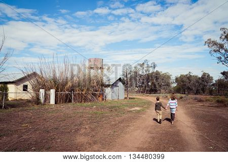 Brother and sister walking down a dirt track in outback Australia