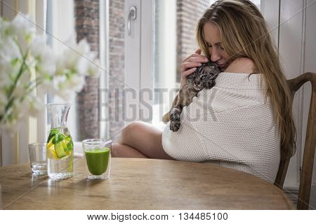 Pretty blonde cuddling her cat in the morning
