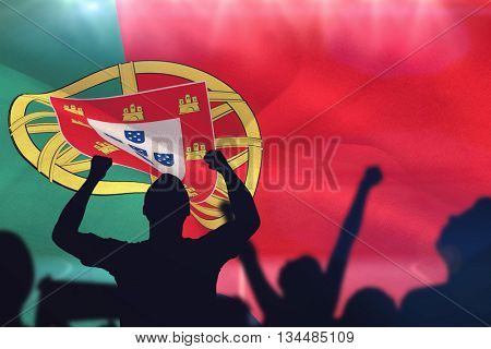 Silhouettes of football supporters against digitally generated portugal national flag