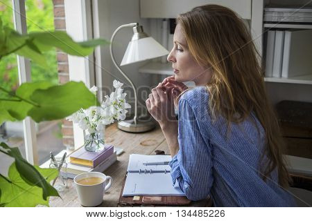 Attractive lady drinking morning coffee in her home office