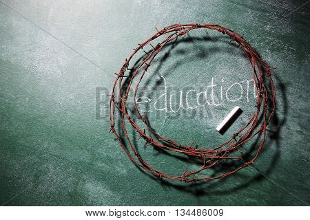 barbwire on top of blackboard with text education