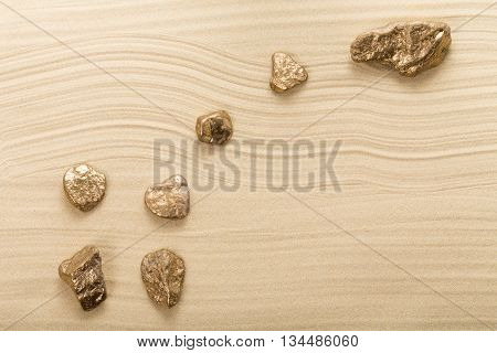Golden stones in form of constellation Ursa Minor on waved sand. Photo can be used as a whole background.