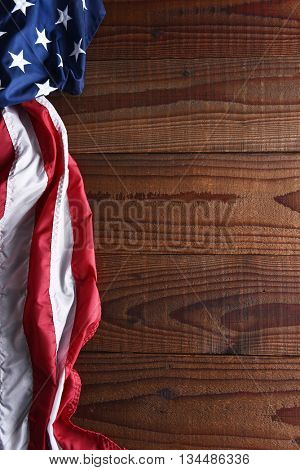 Closeup of an American flag on a dark wood table with copy space. Top view in horizontal format.