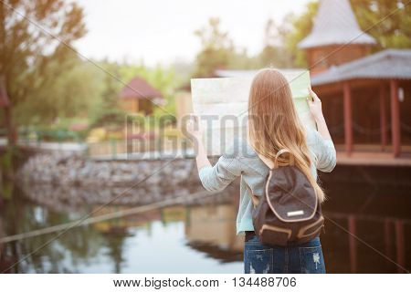 Back side of traveler girl searching right direction on map, orange sunset light, traveling along Europe, freedom and active lifestyle concept