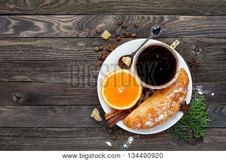 Continental breakfast - cup of hot coffee croissant and orange. Tasty food on rustic wooden background. Top view place for text.