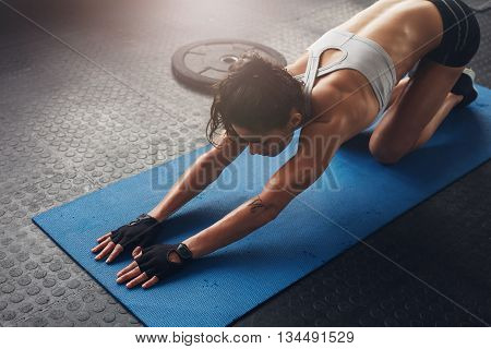 Woman On Fitness Mat Doing Stretching Workout At Gym.