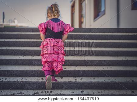Little four years old girl dressed in pink salsa costume  going up the stairs in town
