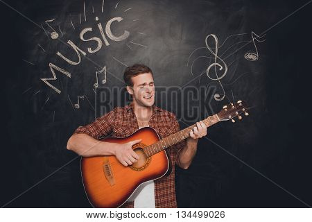 Handsome young instrumentalist playing on the guitar and singer poster