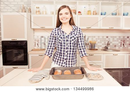 Pretty young smiling housewife in kitchen with baked bread