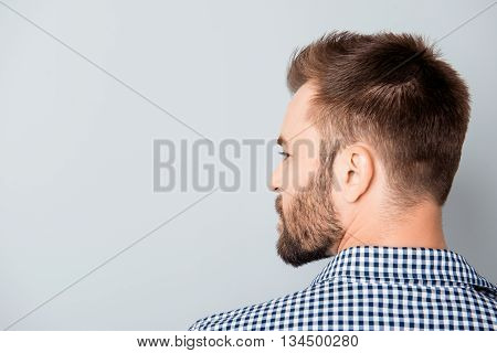 Back View Of Young Bearded Brunet Man On Gray Background