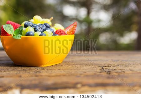 Orange Bowl On Wooden Table, Strawberries, Grapes And Blueberries Inside