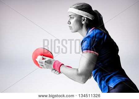 Composite image of female athlete playing ping pong against a grey background