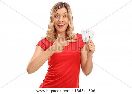 Joyful woman holding four aces and pointing on them with her finger isolated on white background