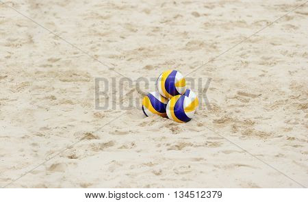 Volleyball beach is a stack of three volleyballs sitting in the sand all ready and waiting for tournament play.
