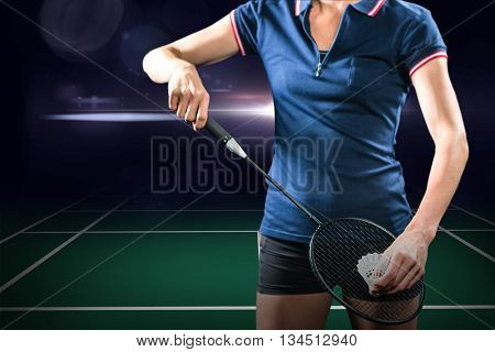 Composite image of badminton player holding a racket ready to serve against dark background