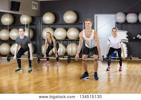 Active Men And Women Lifting Barbells In Gym