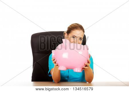 Young female doctor or nurse holding piggybank