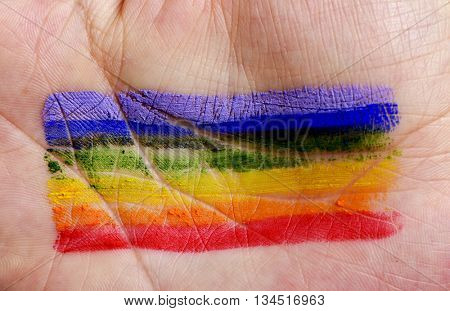 closeup of the palm of the hand of a young caucasian man with a rainbow flag painted in it