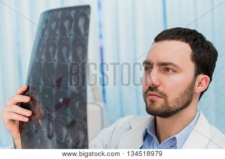 Portrait of mid-adult male doctor in MRI room at hospital.