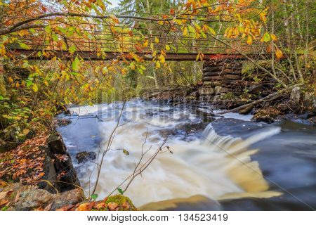 waterfall with trees bridge and rocks in autumn