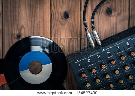 Old phonograph record and mixer device on the wood table