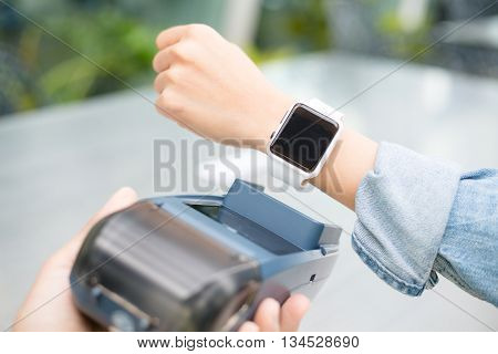 Woman using smart watch to express pay