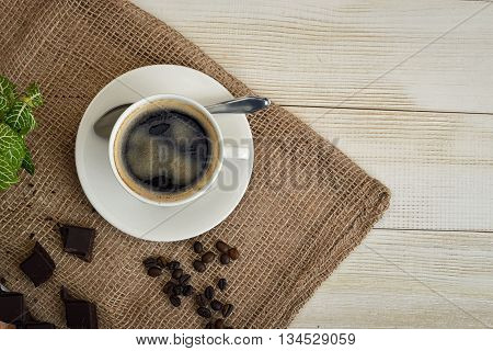 Top view of cup of hot fragrant coffee and coffee beans with chocolate on a mesh fabric. Coffee house. Uplifting mood. Coffee break. Relax. Increasing productivity in the mornings. Coffee breakfast.