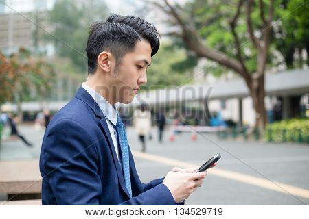 Young business man looking at cellphone