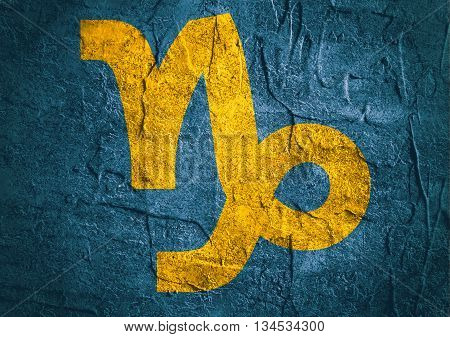 Goat astrology sign. Yellow astrological symbol on concrete textured backdrop