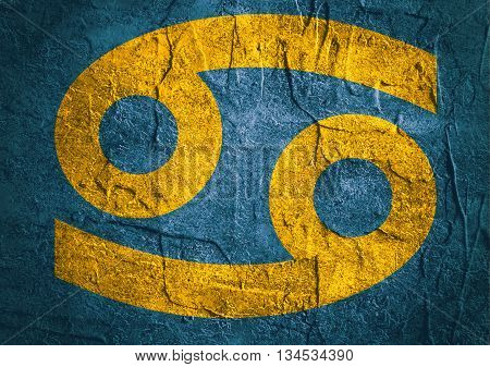 Crab astrology sign. Yellow astrological symbol on concrete textured backdrop