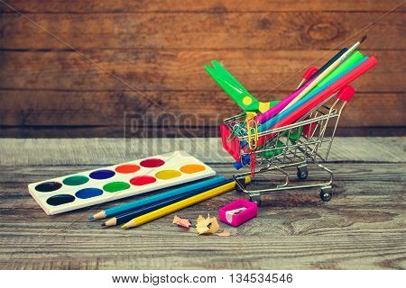 Shopping cart with stationery objects. Office and school supplies.