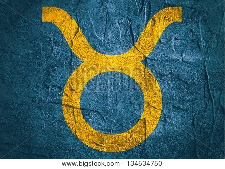 Bull astrology sign. Yellow astrological symbol on concrete textured backdrop