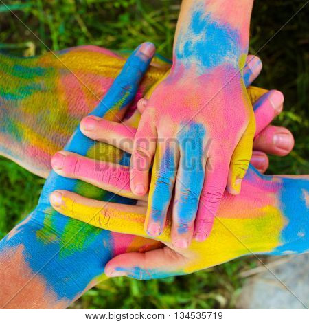 Four hands of family painted in different colors. Concept of love, friendship, happiness in family.