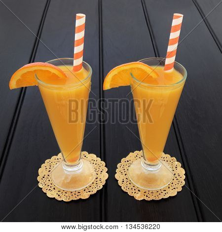 Orange fruit juice drink in glasses on gold doilies with striped straws over dark wood background. High in vitamins and antioxidants.