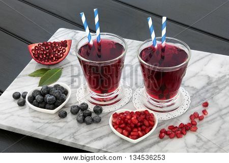 Blueberry and pomegranate juice drink with fresh fruit on marble over dark wood background. High in vitamins, anthocyanins and antioxidants.