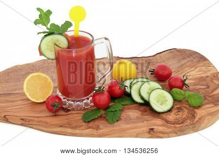Tomato juice health drink with lemon, celery, cucumber, basil and mint herb on an olive wood board over white  background. High in vitamins, anthocyanins and antioxidants.