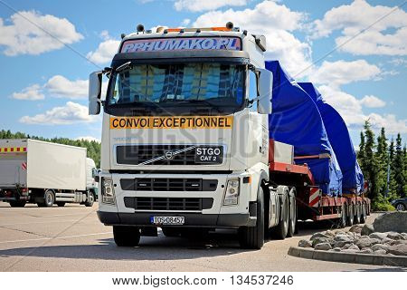 PAIMIO, FINLAND - JUNE 12, 2016: Volvo FH truck with two industrial objects on trailer as oversize load iis parked on a truck stop in South of Finland.