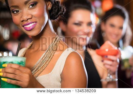 Multicultural group of women after work drinking cocktails in bar