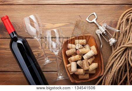 Red wine bottle, wine glasses, bowl with corks and corkscrew. View from above over rustic wooden table background