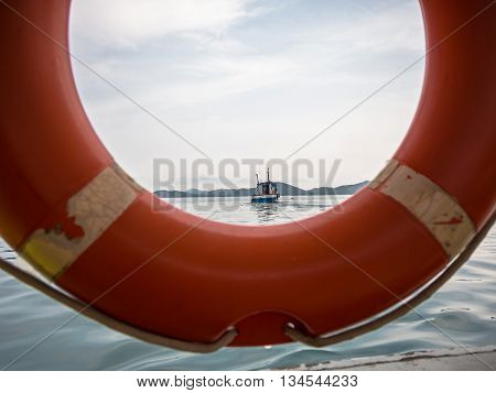 Rescue boat in the sea that look through orange ring buoy