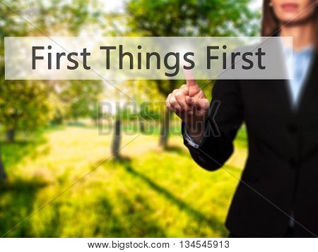 First Things First - Businesswoman Hand Pressing Button On Touch Screen Interface.