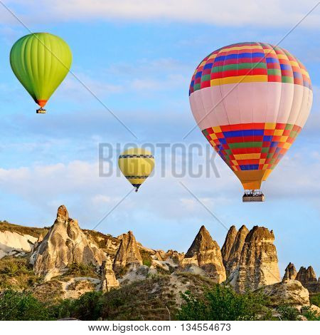 Hot air balloon flying over spectacular landscape of fairy chimneys carved in volcanic tuff by erosion. Cappadocia Turkey