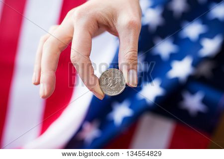 finances, money, crisis, investment and national currency concept - ose up of hands with coins over american flag